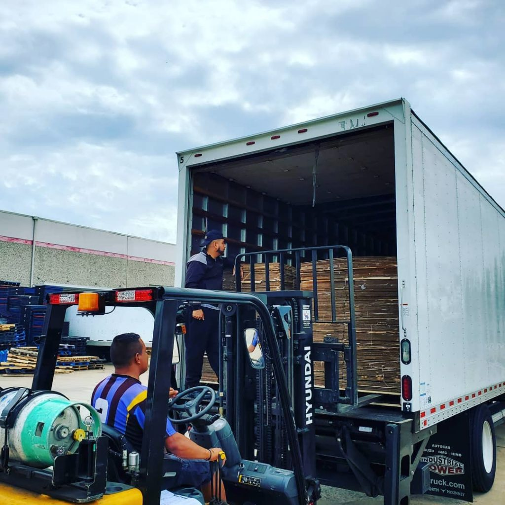 Image: professional movers using a forklift to unload compressed boxes.