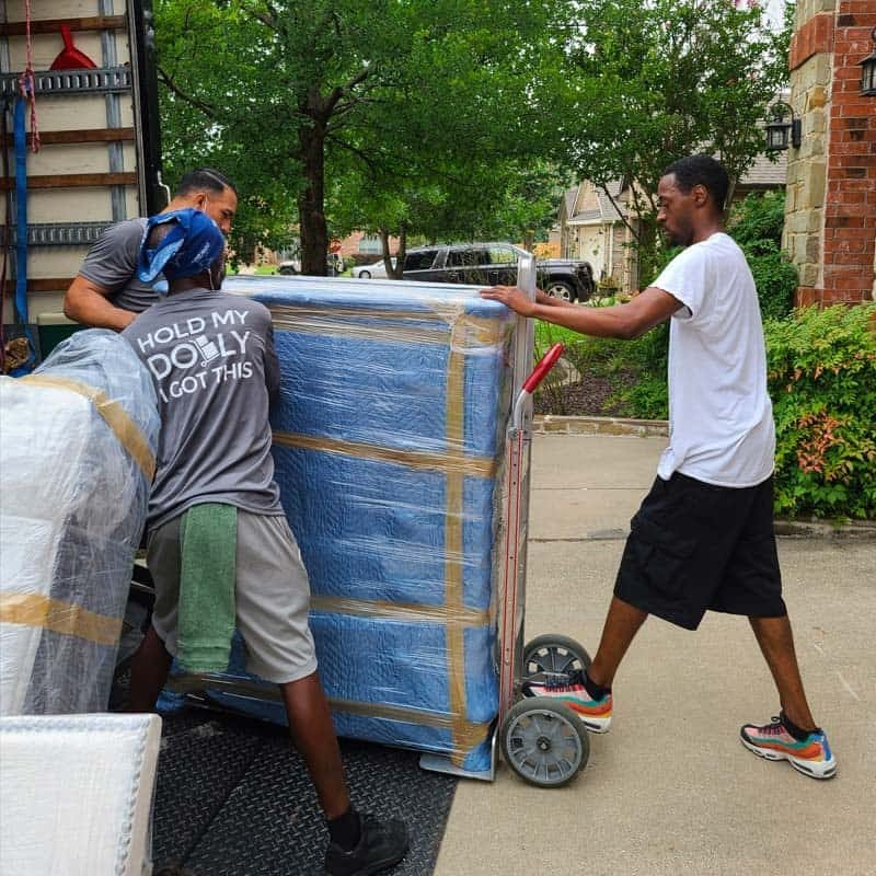 Image: Stonebriar Moving crew loading a large piece of furniture onto a moving truck.