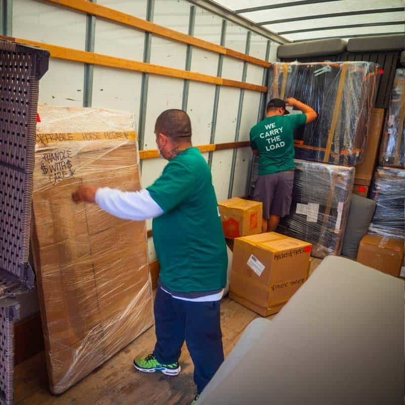 This image shows the Stonebriar Moving crew organizing items in a truck
