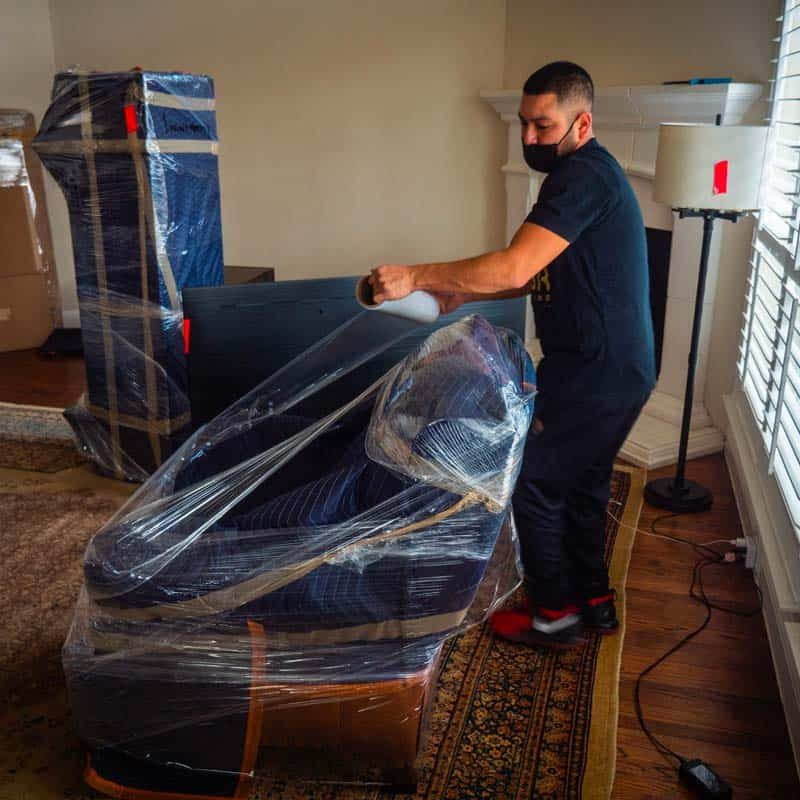 This image shows a moving professional wrapping a sofa.