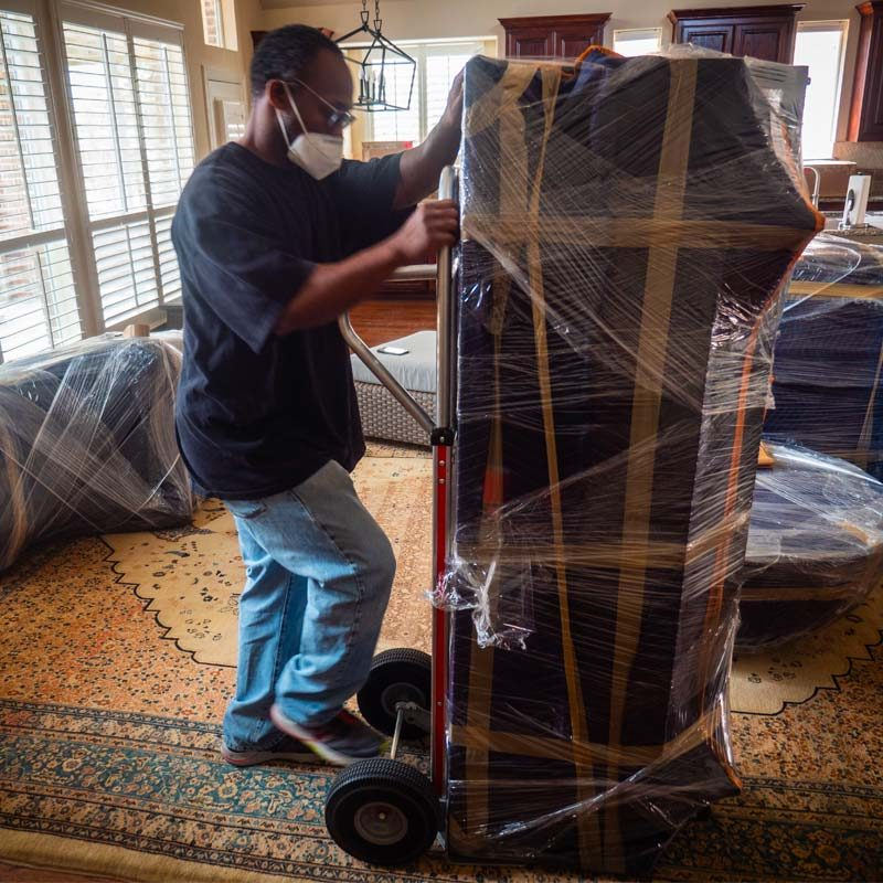 Pictured: a Stonebriar Moving crew member using a dolly for large furniture.
