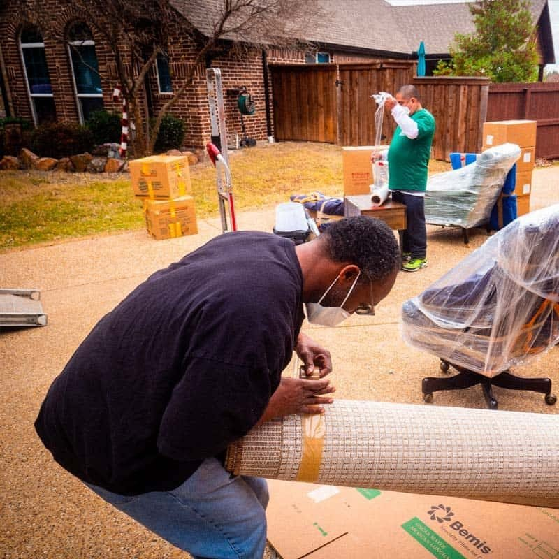 This image shows the Stonebriar Moving crew wrapping boxes and a rug.