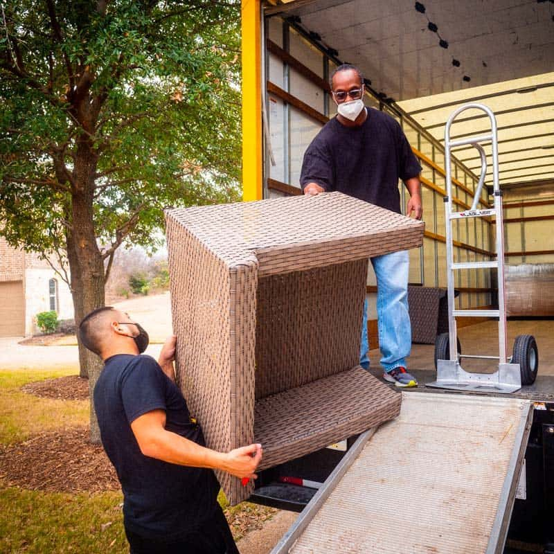 This image shows two Stonebriar Moving crew members loading furniture onto a truck.
